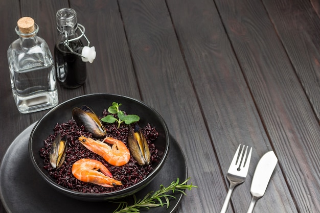 Креветки и мидии с черным рисом в миске. вода и соевый соус в стеклянных бутылках. ложка и вилка на столе. вид сверху. темный деревянный стол.