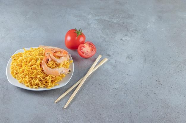 Креветки и лапша на тарелке, на мраморном фоне.