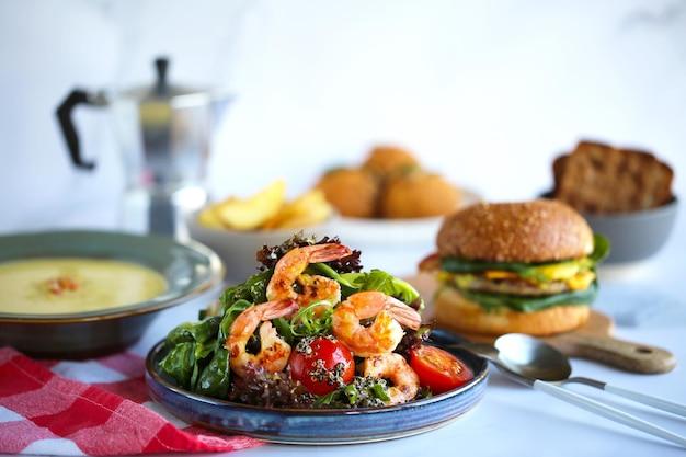 エビとキノアのサラダ美しいおいしいサラダ。テーブルの上にたくさんの食べ物、昼食。適切な栄養。サラダ、ハンバーガー、スープ。食事の日。美しいおいしい料理。キノアのサラダ。お祭りのテーブル。エビのグリル