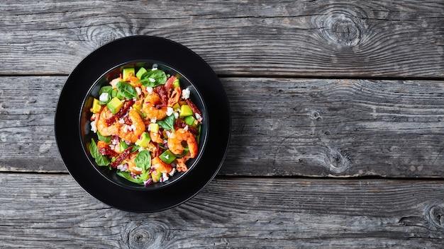 サンドライトマト、砕いたチーズ、素朴な木製のテーブルの上の黒いボウルに赤玉ねぎを添えたエビのアボカドほうれん草のサラダ