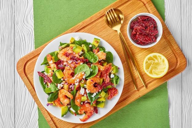 サンドライトマト、砕いたチーズ、木の板の皿に赤玉ねぎを添えたエビのアボカドほうれん草のサラダ