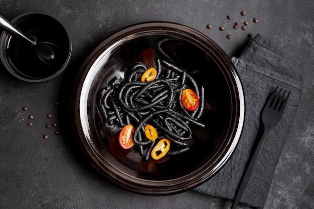 Черная паста с креветками в тарелке с вилкой и соевым соусом