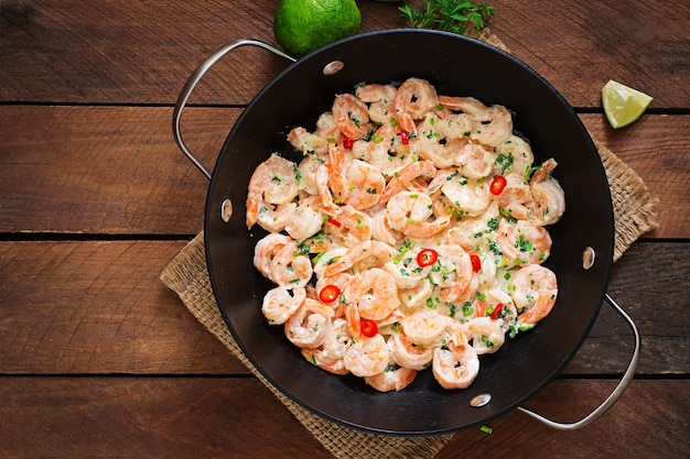 Shrimp in a creamy garlic sauce with parsley and lime in a frying pan. top view