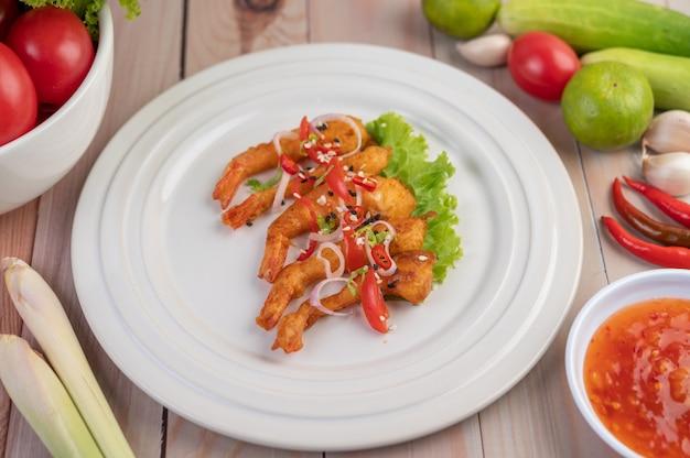 Креветки во фритюре, красиво оформленные в белом блюде.