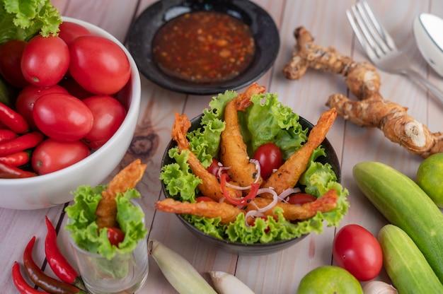 木製のボウルにサラダとトマトの上に置かれたエビの揚げ衣。