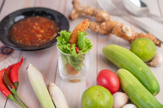 Креветки во фритюре, помещенные в салат и помидоры в деревянной миске.