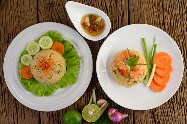 Жареный рис с креветками на белой тарелке на деревянном столе