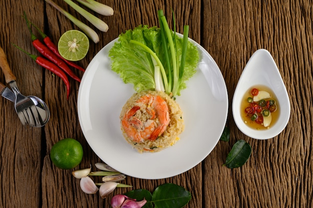 Shrimp fried rice on a white plate on a wooden table