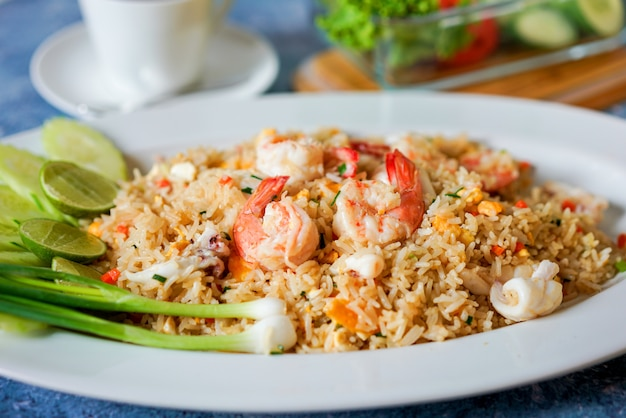 Shrimp fried rice with lime and coriander on blue table whit white coffee cup and  vegetable