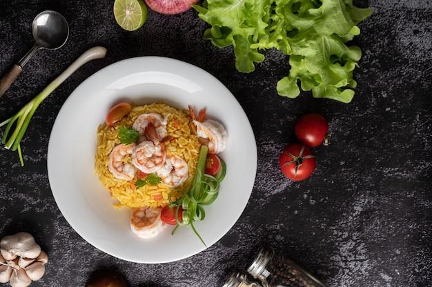 Жареный рис с креветками с помидорами, морковью и зеленым луком на тарелке