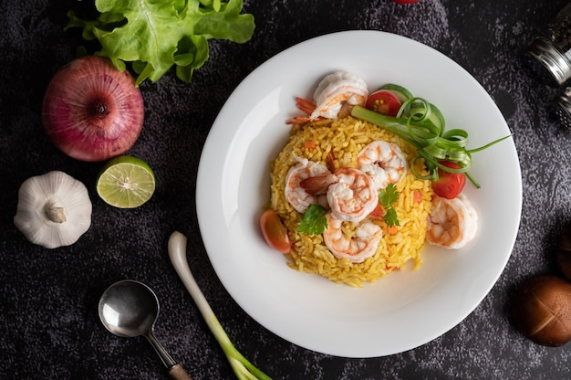 Shrimp fried rice with tomatoes, carrots and scallions on the plate
