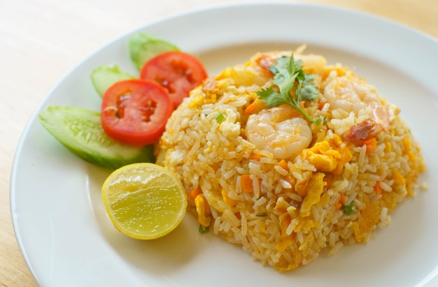 Shrimp fried rice with tomatoes, cucumbers and lemon .