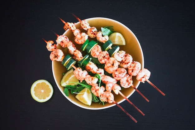 Shrimp kebabs on wooden skewers with zucchini