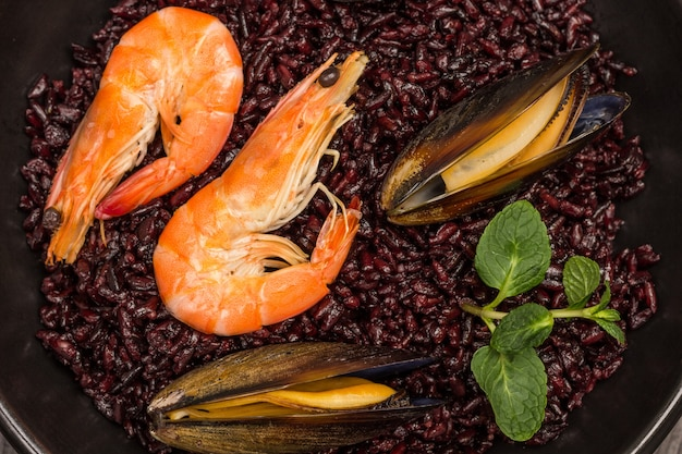 Shrimp and mussels with black rice in bowl. flat lay. close up