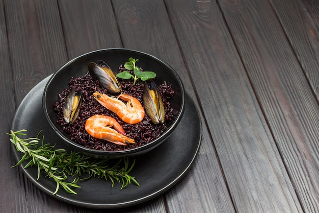Shrimp and mussels with black rice in bowl. top view. dark wooden table.