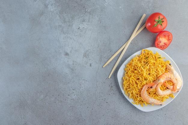 Gamberetti e noodle su un piatto, sullo sfondo di marmo.