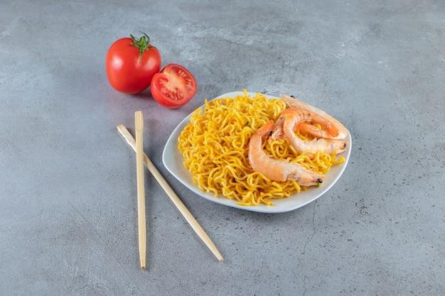 Gamberi e noodle su un piatto, sulla superficie di marmo.