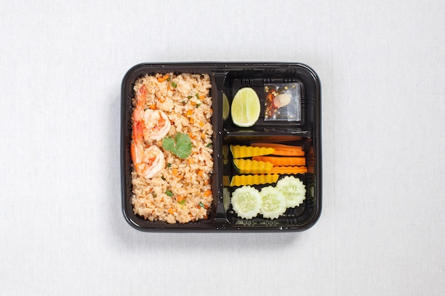 Shrimp oil fried rice with shrimp put in black plastic box, put on a white tablecloth, food box