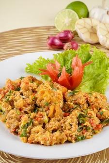 Креветки или креветки с соусом из соленых яиц на белой тарелке и ингредиенты