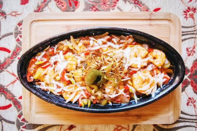 トルコのトルコ料理のボウルテーブルレストランにオニオンペッパートマトのエビパスタ