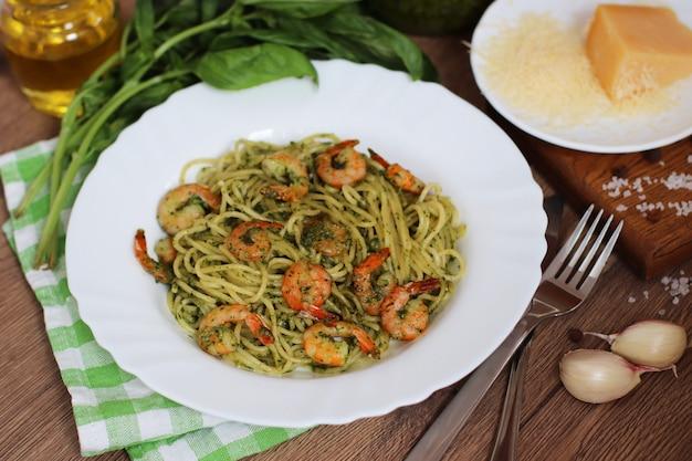 Shrimp pesto pasta with ingredients in rustic style