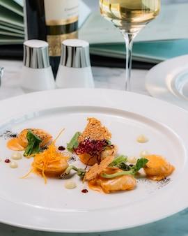 Piatto di gamberi guarnito con salsa di pane ripieno di spinaci e carota grattugiata