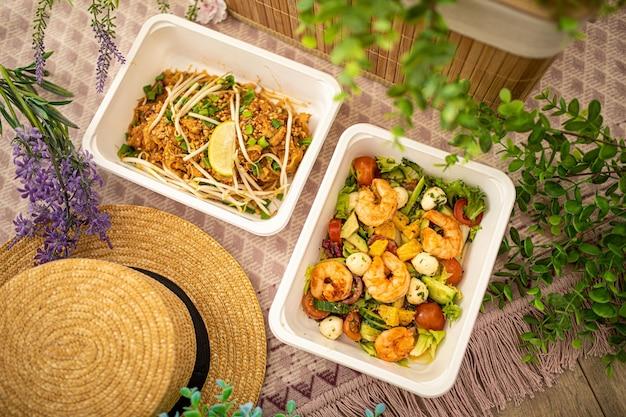 새우 샐러드와 아시안 팟 타이. 자연스러운 장식으로 구성. 사무실 또는 일회용 플라스틱 접시에 피크닉에 대한 개념 음식 배달.