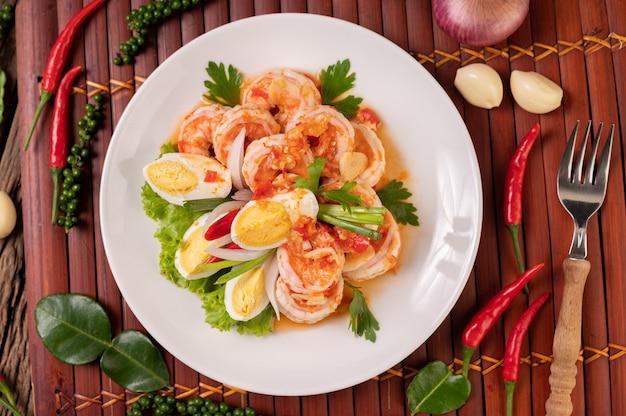 Салат из креветок с отварным яичным салатом и нарезанным зеленым луком в белой тарелке