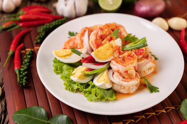 Shrimp salad with boiled egg lettuce and chopped scallions in a white plate
