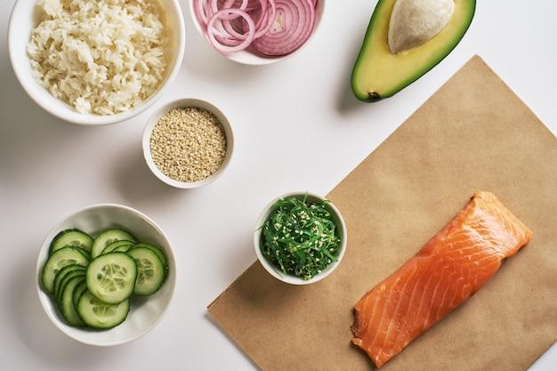 Shrimp salmon poke bowl on craft paper, chuka salad, white rice, cucumber