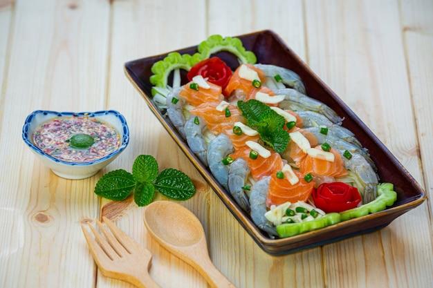 Gamberetti e insalata di salmone piccante su una superficie di legno