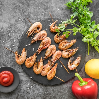 Shrimp skewers with sauce on table