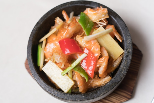 Shrimp stir fry in a wok with serving plates in the