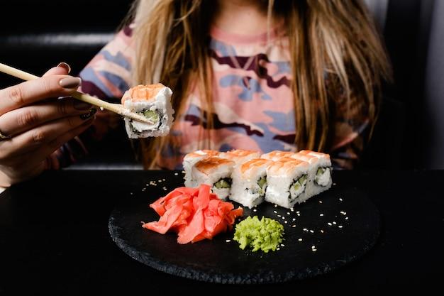暗い背景にエビ巻き寿司をセット。アジア料理の食事。伝統的な東洋料理。健康的な栄養。箸でロールを保持している女性