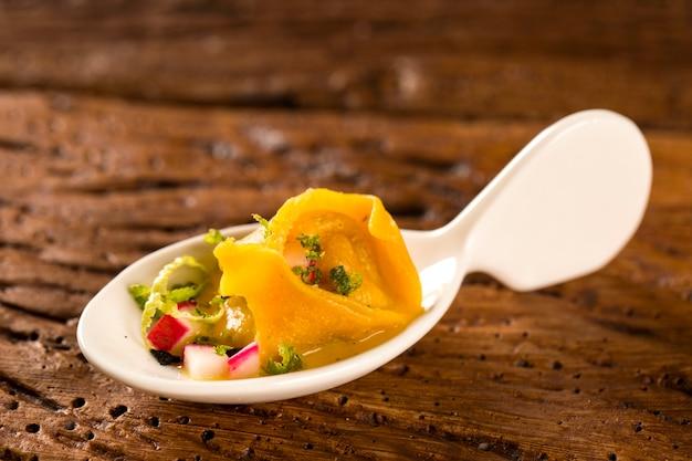 Тортеллине с креветками, утренний соус, редис и черная соль по ложке. вкус гастрономической еды руками