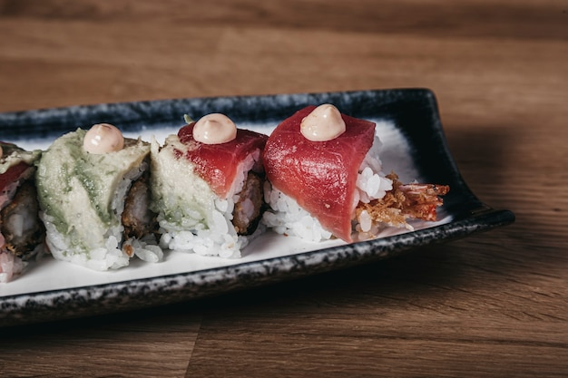 Shrimp uramaki topped with tuna tataki.