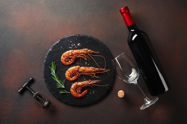 Shrimp with a bottle of wine. top view. free space for your text. on the old background
