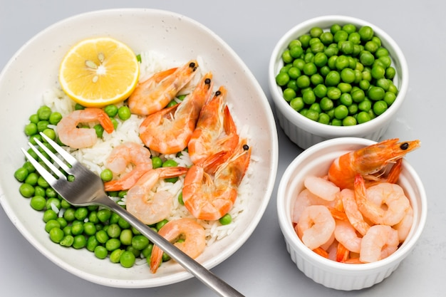Shrimp with green peas in gray bowl. shrimp and green peas in bowls. top view.