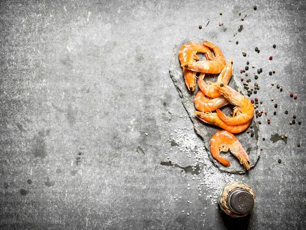 石のテーブルに胡椒と塩を添えたエビ。
