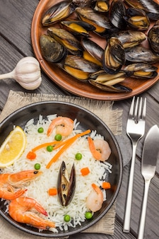 Shrimp with rice in black bowl. mussels in ceramic plate. garlic, fork with knife on table. top view.