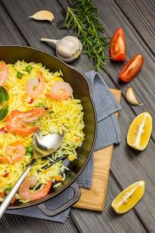 Креветки с рисом на сковороде. чеснок, дольки лимона и помидор на столе. вид сверху.