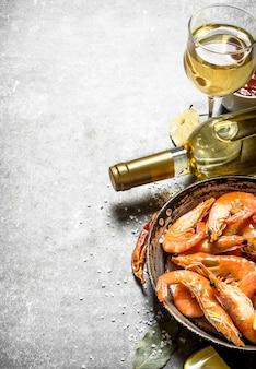 Креветки с белым вином и лимоном. на каменном столе.