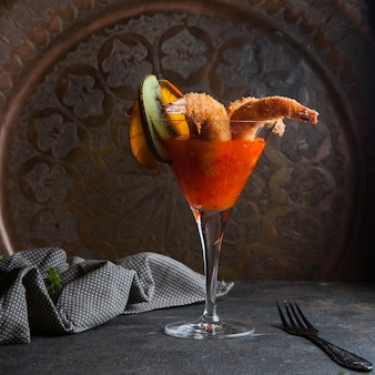 Shrimps in batter with spicy sauce and rag and fork in cocktail glass