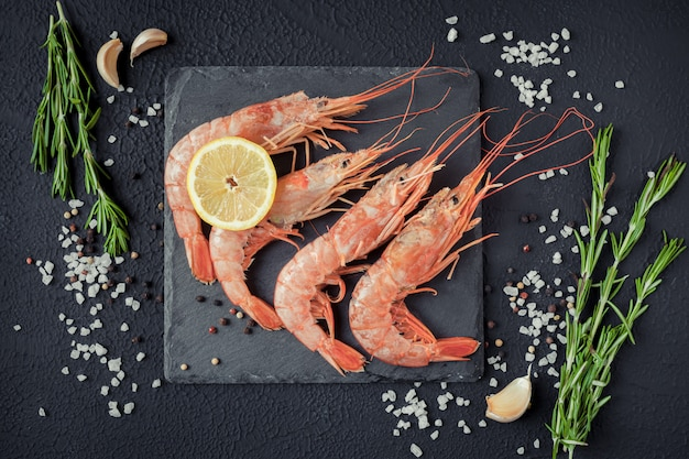 Shrimps on a black background with spices
