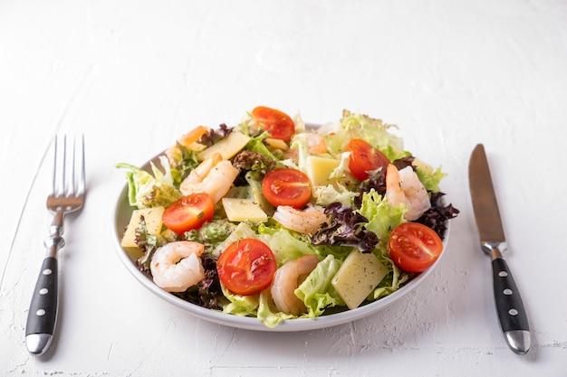 エビ、チェリートマト、レタス、チーズを皿に盛り付けます。健康とダイエット食品の概念