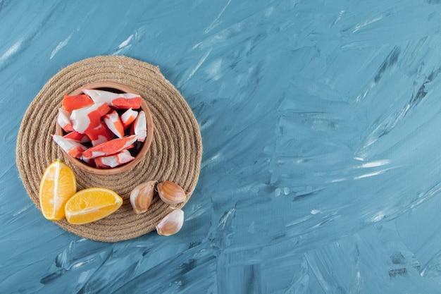 대리석 배경에 있는 트리벳에 얇게 썬 레몬과 마늘 옆에 있는 그릇에 새우.