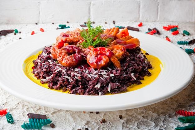 Креветки в кляре с красным рисом и зеленью в белой тарелке