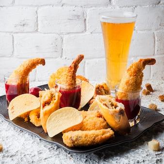 Креветки в кляре с соусом и чипсами и пиво в тарелке
