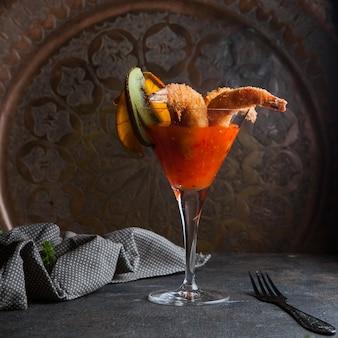 Креветки в кляре с острым соусом и тряпкой и вилкой в бокале для коктейля