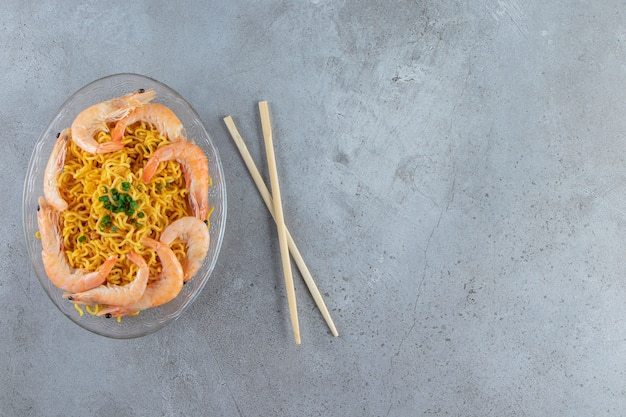 Shrimps and noodle on a glass dish next to chopsticks, on the marble background.